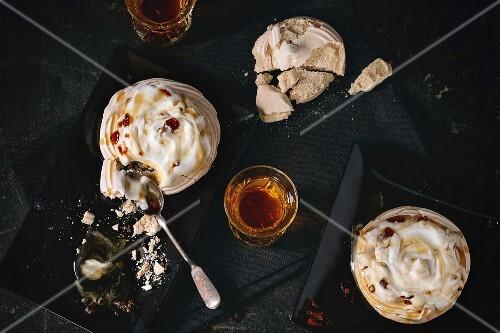 Kleine Karamell-Pavlova (Meringue-Dessert) mit Karamellsauce