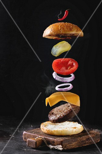 Flying ingredients for homemade burger on little wooden cutting board over dark background