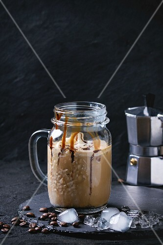 Glass mason jar of ice coffee with ice cream and chocolate sauce