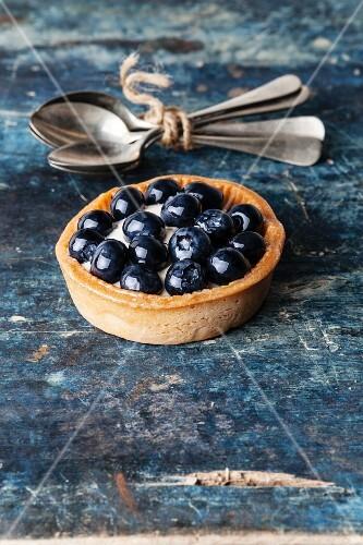 Blueberry tart on blue wooden background