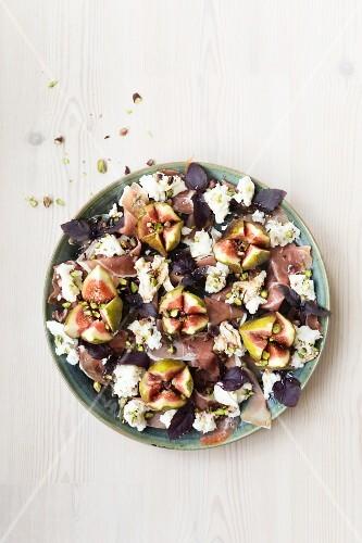 Fig prosciutto and mozarella salad with purple basil and balsamic vinegar pistachio nuts
