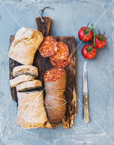 Brot und Salami auf rustikalem Holzbrett (Aufsicht)