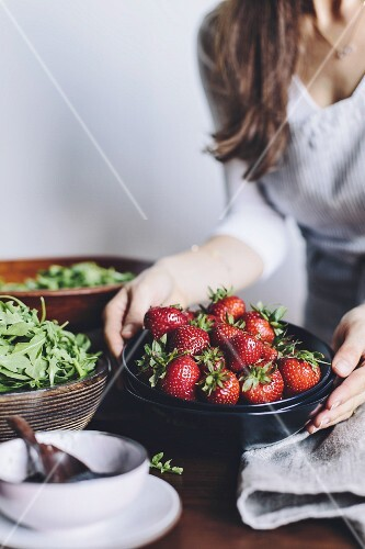 A woman is placing a bowl of strawberries on a table, getting ready to put together a strawberry and spinach salad