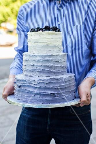 A man holding a three-tiered wedding cake