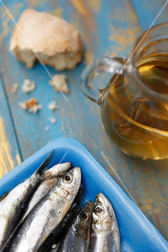 Fresh sardines in a blue Styrofoam dish with olive oil and bread
