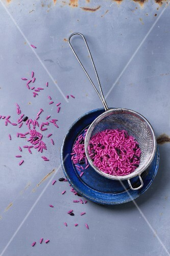 Uncooked pink and black rice on blue ceramic plate with sieve over gray metal surface
