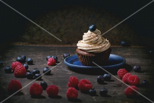 Chocolate cupcake with butter coffee cream and fresh berries over dark background