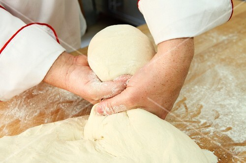 A piece of soft dough being twisted off by hand