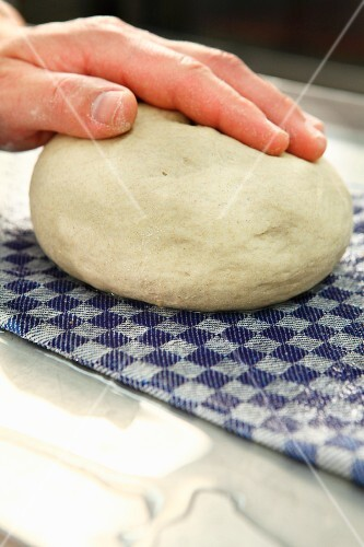 Dough being rolled over a wet cloth to moisten it