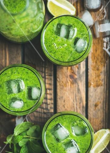 Grüner Smoothie mit Eiswürfeln und Minze in Gläsern (Aufsicht)