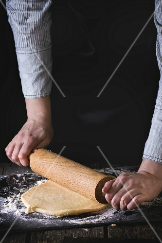 Female hands rolling out dough for pasta by wooden rolling pin over wooden kitchen table, powdering by flour