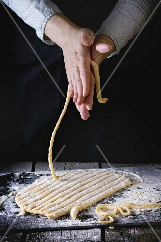 Female hands making pasta pici over wooden kitchen table, powdering by flour