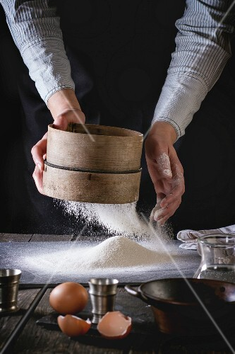 Female hands sifting flour from old sieve on old wooden kitchen table