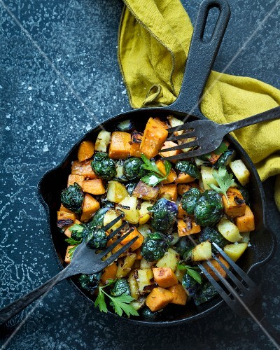 Fried sweet potato, potato and brussels sprouts with leaf parsley