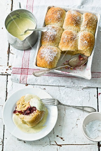 Sweet rolls made of yeast dough, filled with berry jam and served with custard