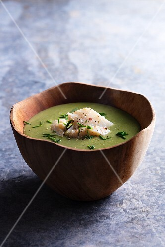 Pea soup with cod in a wooden bowl