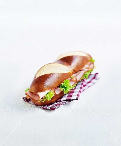 A lye bread sandwich with ham and lettuce