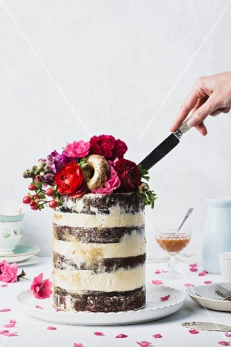 Wedding cake with buttercream, flowers, and gold donuts being cut