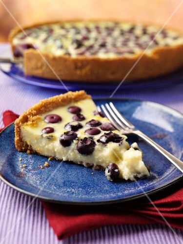 A slice of blueberry lemon pie on a plate with a whole pie in the background