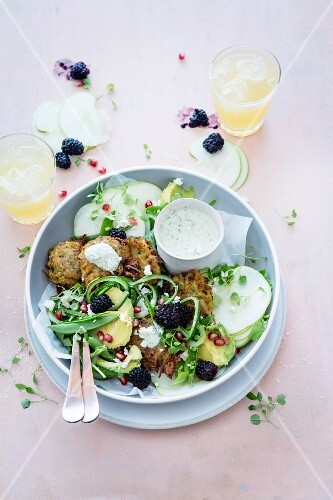 Crispy potato cakes on a bed of vegetables with avocado, blackberries and pomegranate seeds