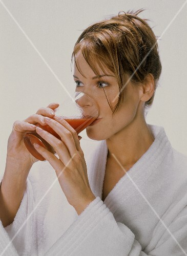 Young woman drinking tomato juice from tall glass