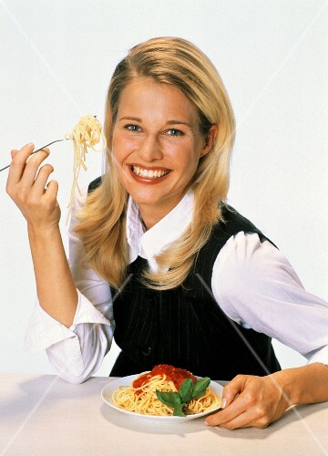 Young woman eating spaghetti with tomato sauce