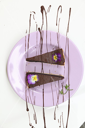 Two pieces of chocolate tart with horned violets