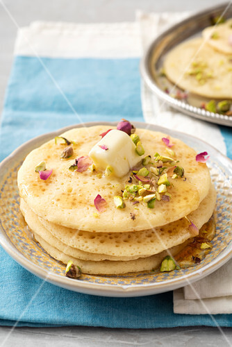 Moroccan baghrir with honey, pistachio nuts, rose petals and rose water