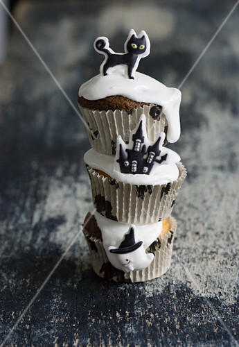 Chocolate muffins decorated with icing and a sugar haunted house, a black cat and a ghost