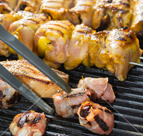 Dates in bacon and meat kebabs on a barbecue