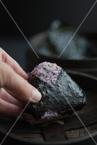 A hand holding onigiri with red shiso (Japan)