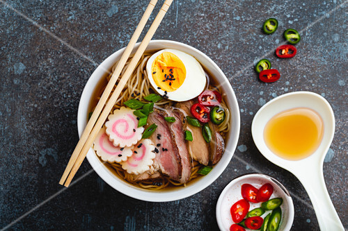 Cooking Japanese noodle soup ramen. Ramen with sliced pork, narutomaki, egg and kitchen spoon with broth on rustic stone background