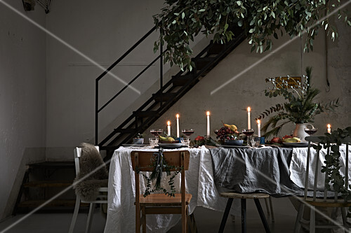 Festively set, candlelit dining table in loft-apartment interior