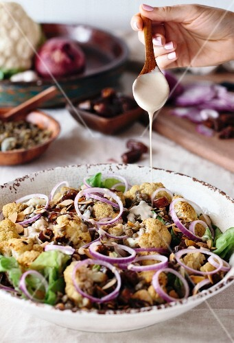 A woman is drizzling a bowl of roasted cauliflower salad with tahini dressing