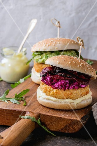 Two vegetarian hamburgers with onion and cheese cutlets, avocado salad, arugula, fried beetroot and yogurt sauce
