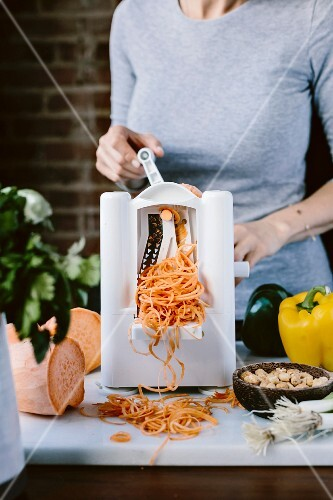 A woman is spiralizing sweet potato to turn them into noodles