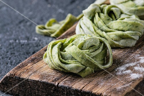 Fresh raw uncooked homemade twisted green spinach pasta tagliatelle with flour