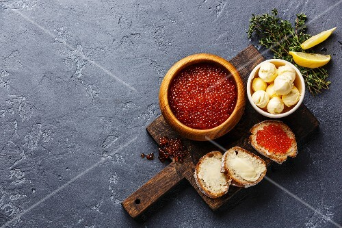 Salmon red caviar in wooden bowl and Sandwiches on dark stone background copy space