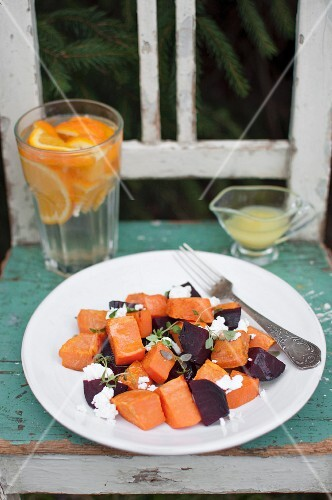 Roasted vegetables salad made of sweet potato and beetroot with goat cheese and orange vinaigrette