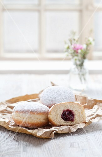 Jam doughnuts on a paper bag next to a window