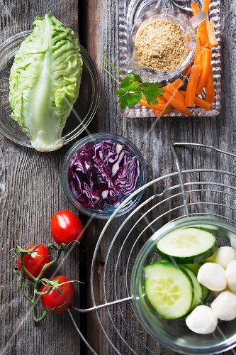 Ingredients for couscous salad with red cabbage, lettuce hearts, carrot, tomato, cucumber, mozzarella and parsley