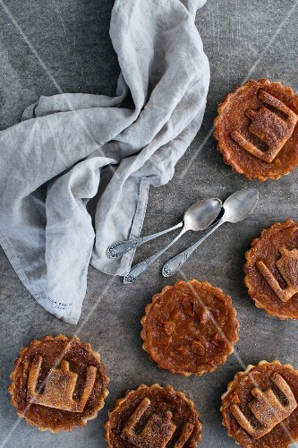 Several apple tartlets with a pastry decoration on the top