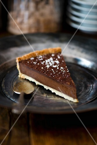 A piece of dark chocolate tart on a pewter plate with an antique spoon (France)