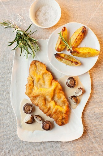 Schnitzel in white wine and mushroom sauce with potato wedges