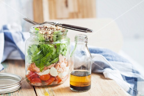 A mixed salad with plum tomatoes, mozzarella balls, salmon, lettuce and toasted hazelnuts, with a balsamic and hazelnut oil dressing in a glass jar