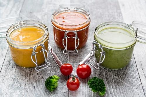 Verschiedene bunte Suppen im Glas (Brokkolisuppe, Tomatensuppe, Kürbissuppe)