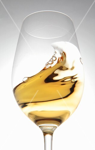 White wine in a glass with a wave