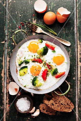 Pan of fried eggs, broccoli and cherry-tomatoes with bread on old green background