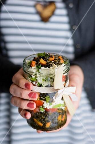 Frau hält Einmachglas mit Belugalinsensalat in den Händen