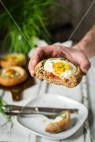 A hand holding a bread roll filled with a fried egg